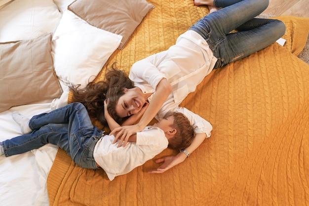 暖かく居心地の良いシーン、ママと息子は笑顔で抱き締めてベッドで休んでいます。子供の頃の思い出のコンセプト。