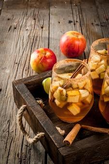 Warm apple sangria, apple cider with pieces of fruit, cinnamon, spices, sugar