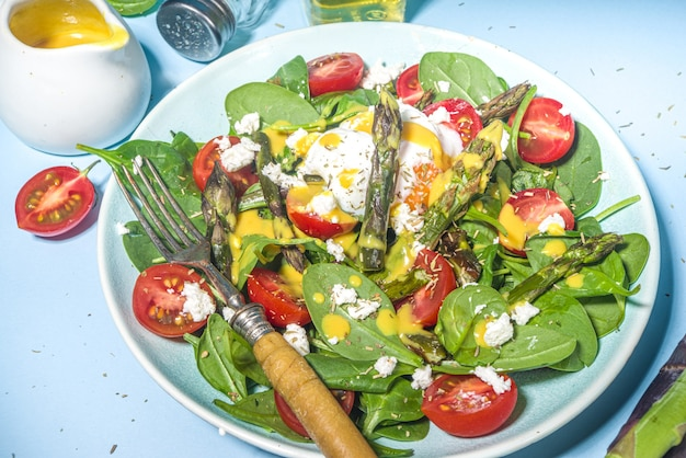 ほうれん草、チェリートマト、フェタチーズ、ポーチドエッグの温かいアスパラガスサラダ