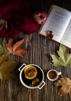 暖かい秋と冬のアルコール飲料のホットワイン。蜂蜜、紅葉、リンゴ、本、木製の背景にウールのセーター。秋の居心地の良いムード。秋の背景。フラット横たわっていた。垂直
