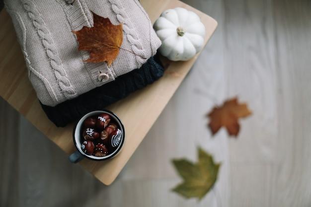 Теплый осенний фон с вязаной одеждой и осенними листьями