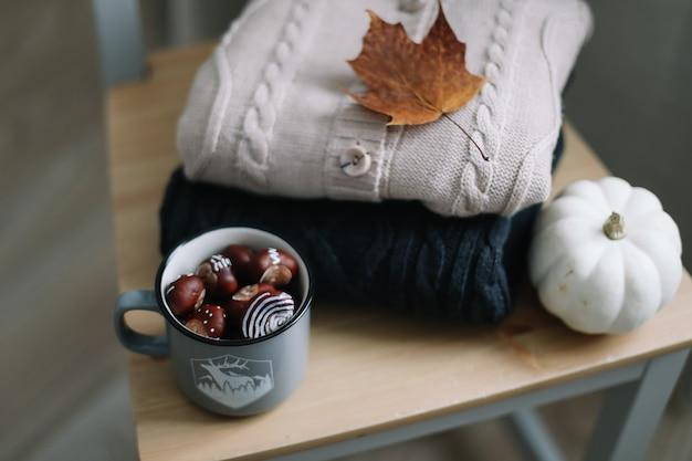 Теплый осенний фон с вязаной одеждой и осенними листьями Premium Фотографии