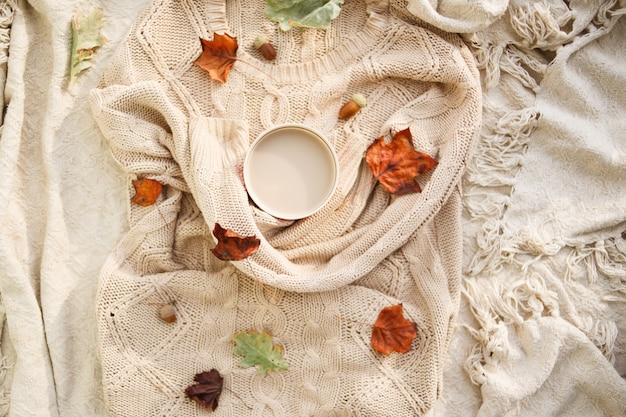 Warm autumn. cup of coffee wrapped in a woolen beige sweater. still life.