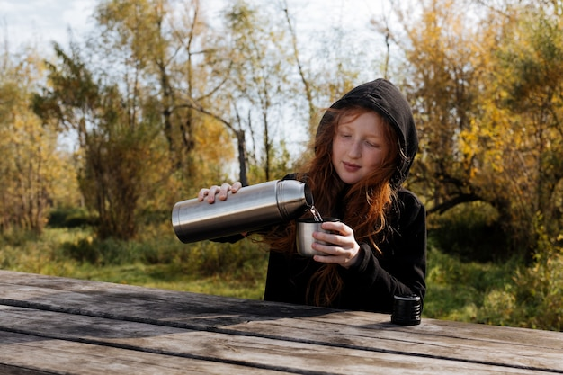 On a warm autumn day, a red-haired girl pours hot tea