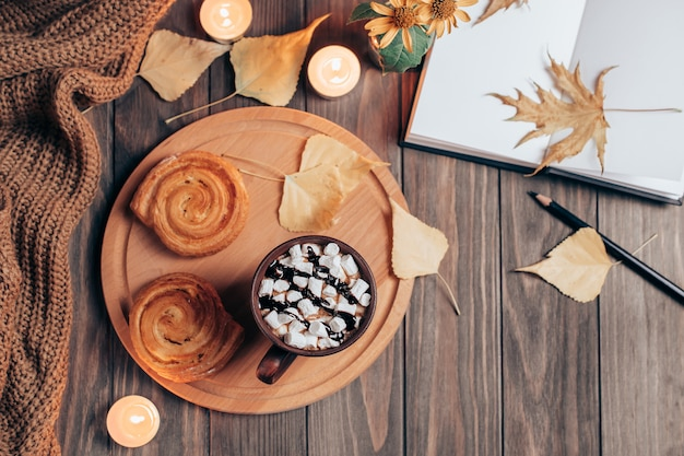 Warm autumn hygge composition with hot chocolate, pastry and notebook on wood