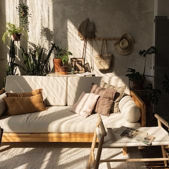 따뜻한 boho 스타일의 현대적인 홈 인테리어 디자인. 소파, 베개, 가정 식물, 카펫 및 콘크리트 벽 장식