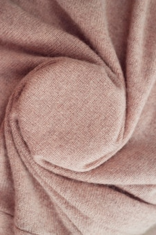 Warm cashmere fabric texture folded background with natural knitted material