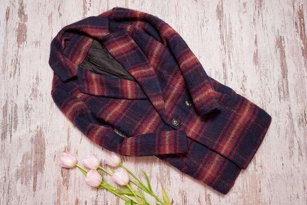 暖かい市松模様のコートとチューリップ。ファッショナブルなコンセプト、木製の背景