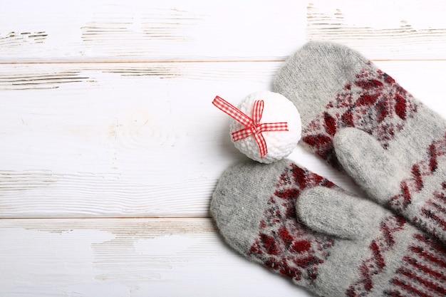 Тёплое рождество. вязаные варежки и елочная игрушка. новогодний праздник фон