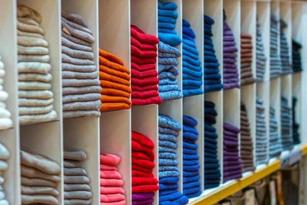 따뜻한 옷은 선반에 깔끔하게 접었습니다. 쇼룸이나 상점에서 다채로운 점퍼, 가디건, 스웨트 셔츠, 스웨터, 후드 행.