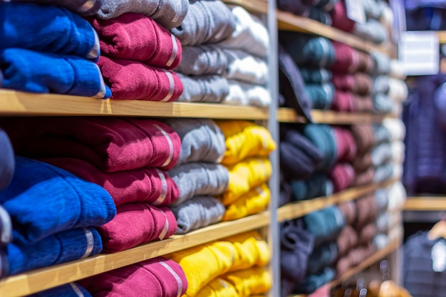 Warm clothing neatly folded on a shelf. a row of colorful jumpers, cardigans, sweatshirts, sweaters, hoodies in the showroom or store.