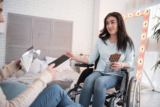 Теплый разговор. позитивная женщина-инвалид и подруга едят плитку шоколада и болтают