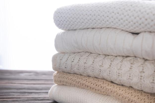 暖かくて居心地の良い服が積み上げられています。さまざまなニットパターンの背景のクローズアップ。秋または冬のコンセプト。