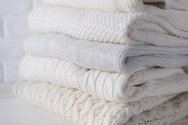 Теплая уютная одежда светлых тонов с крупным планом разных вязаных узоров