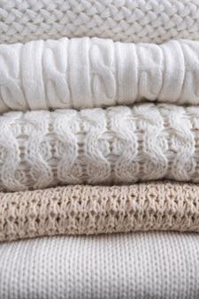 Теплая уютная одежда с разными вязаными узорами крупным планом. осенний или зимний фон.