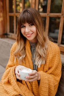 Теплый уютный портрет счастливой мечтательной женщины с волнистыми волосами, покрытой желтым пледом и держащей чашку горячего капучино. белая женщина отдыхает на террасе.