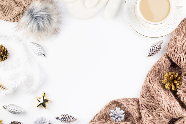 Warm, cozy winter clothing, hot drink and christmas decorations on white