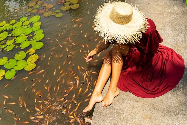 따뜻한 날. 그녀의 휴가를 즐기고 호수 근처를 산책하는 동안 세련된 모자를 쓰고 친절한 여성 사람