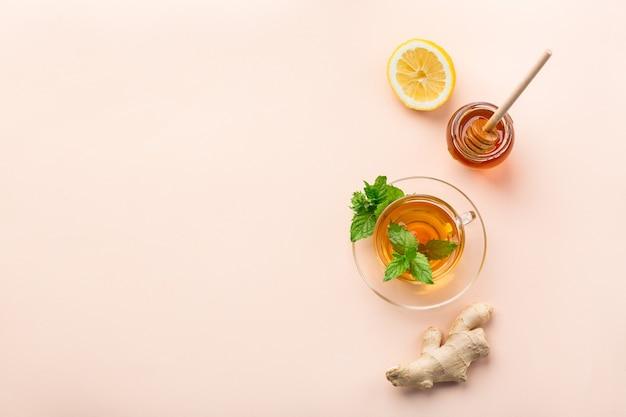 Теплый настой напитка в стакане при простуде в зимние осенние дни. чашка имбирного чая с мятой, лимоном и медом на коралловом столе. копирование пространства, плоский фон