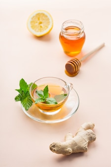 추운 독감 겨울 가을 날을 위해 유리에 따뜻한 음료 음료 주입. 산호 테이블에 민트, 레몬, 꿀을 넣은 생강차 한 잔