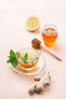Теплый настой напитка в стакане при простуде в зимние осенние дни. чашка имбирного чая с мятой, лимоном и медом на коралловом столе