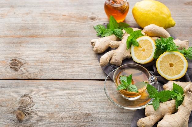 추운 독감 겨울 가을 날을 위해 유리에 따뜻한 음료 음료 주입. 나무 테이블에 민트, 레몬, 꿀을 넣은 생강차 한 잔, 복사 공간