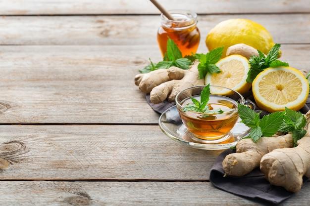 Теплый настой напитка в стакане при простуде в зимние осенние дни. чашка имбирного чая с мятой, лимоном и медом на деревянном столе, копией пространства