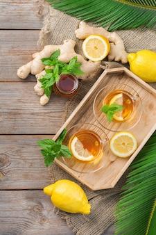 Теплый настой напитка в стакане при простуде в зимние осенние дни. чашка имбирного чая с мятой, лимоном и медом на деревянном столе, плоская планировка