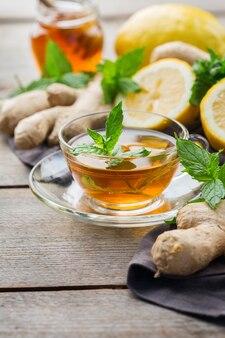 추운 독감 겨울 가을 날을 위해 유리에 따뜻한 음료 음료 주입. 나무 탁자에 민트, 레몬, 꿀을 넣은 생강차 한 잔