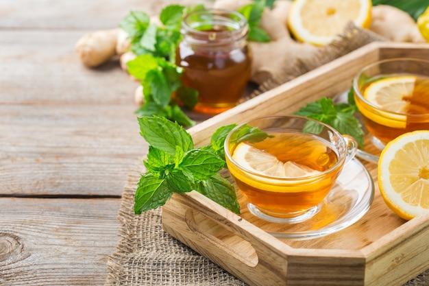 Теплый настой напитка в стакане при простуде в зимние осенние дни. чашка имбирного чая с мятой, лимоном и медом на деревянном столе
