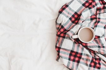 Warm drink in squared plaid on bedsheet