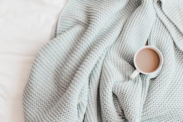 Warm drink in knitting blue plaid on bedsheet