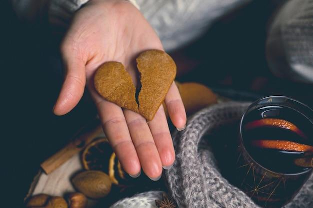 寒い季節の温かい飲み物、グラス一杯のグラントワインとハート型のクッキーを持った女の子