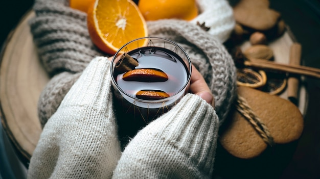 寒い季節の温かい飲み物、女性の手にグラス1杯のグラントワイン、テーブルの上にオレンジ、クッキー、スパイス、暖かいスカーフ
