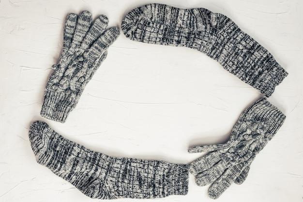 暖かい女性の灰色のニット手袋、白いテクスチャ背景に丸いフレームの靴下。フラットレイ、トップビューの最小限のファッションコンセプト。