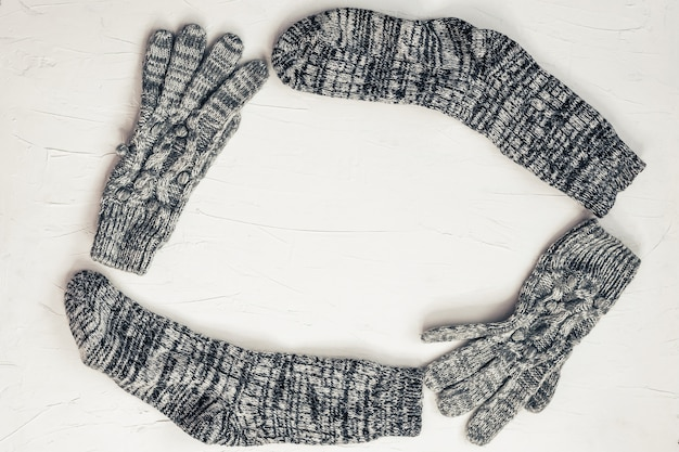 Warm female gray knitted gloves, socks of round frame on white textured background. flat lay, top view minimal fashion concept.