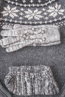 Warm female gray knitted gloves, socks on a sweater textured vertical banner background. flat lay, top view minimal fashion concept.