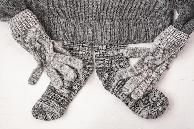 Warm female gray knitted gloves, socks on a sweater on white textured background. flat lay, top view minimal fashion concept.