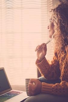 暖かいフィルターカラーの女性が窓の外を見て、ノートパソコンを持って自宅で仕事をし、リラックスしてコーヒーや紅茶を飲む