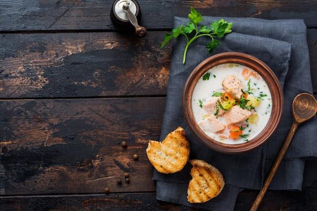 오래 된 나무 배경에 오래 된 세라믹 그릇에 야채와 연어 따뜻한 핀란드어 크림 수프. 소박한 스타일. 평면도.