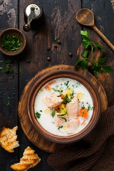 오래 된 나무 표면에 오래 된 세라믹 그릇에 야채와 연어 따뜻한 핀란드어 크림 수프. 소박한 스타일. 평면도.