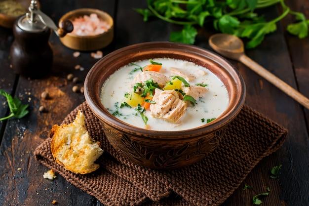 오래 된 나무 표면에 오래 된 세라믹 그릇에 야채와 연어 따뜻한 핀란드어 크림 수프. 소박한 스타일.
