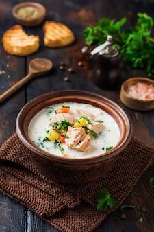 오래된 세라믹 그릇에 연어와 야채를 넣은 따뜻한 핀란드 크림 수프