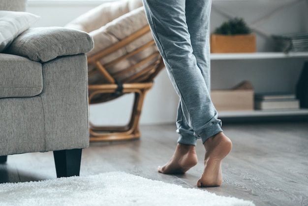 따뜻한 바닥 개념입니다. 집에서 나무 바닥을 밟는 여성 다리 클로즈업