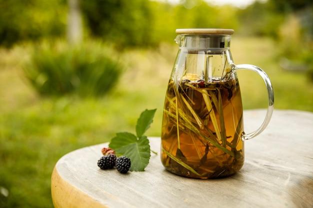 가을날 나무 책상에 따뜻한 유리 찻주전자, 녹차 잎, 레몬그라스. 근접 촬영 이미지입니다.