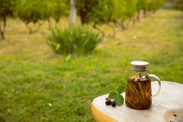 따뜻한 유리 찻주전자, 녹차 잎, 레몬그라스가 농장의 나무 책상 위에 있고, 텍스트를 위한 빈 공간이 있습니다.