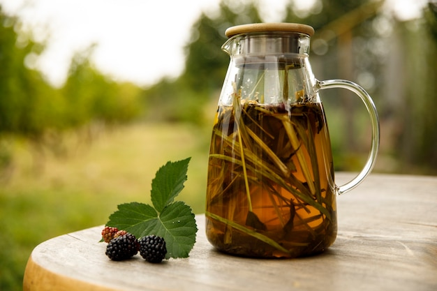 Warm glass teapot, green tea leaves and lemongrass on the wooden desk at morning in plantations with long banner background empty space for text, organic product from the nature for healthy.