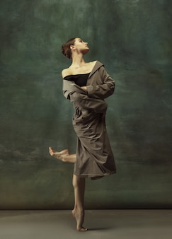 Warm. graceful classic ballerina dancing, posing isolated on dark studio background. stylish trench coat. grace, movement, action and motion concept. looks weightless, flexible. fashionable, style.