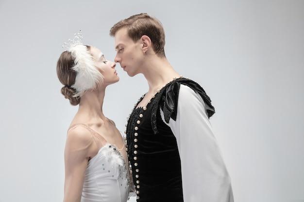 暖かい。白いスタジオの背景に分離して踊る優雅なクラシックバレエダンサー。白鳥のキャラクターのような柔らかい白い服を着たカップル。優雅さ、芸術家、動き、行動、動きの概念。