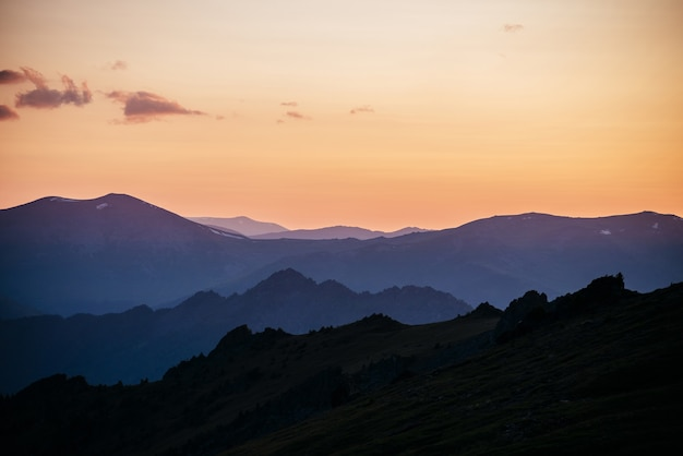 Warm gradient of dawn sky above layers of mountain and rock silhouettes.